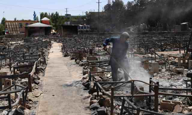 A man clears debris after Taliban militants burned a market in Ghazni. Photograph Zakeria HashimiAFPGetty Images