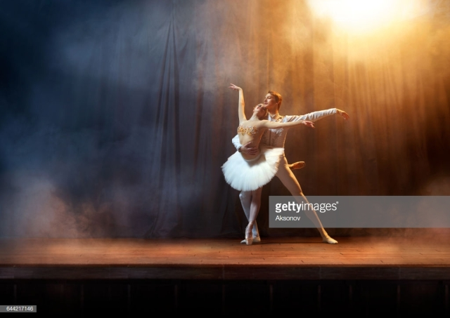 Title Classical ballet dancers performing on stage theatre. There is a fog on the stage.